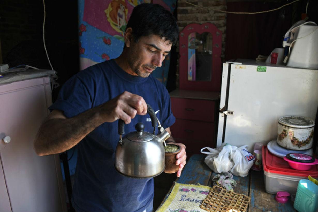 Sánchez, en su cocina cebando mates (Crédito: Clarín)
