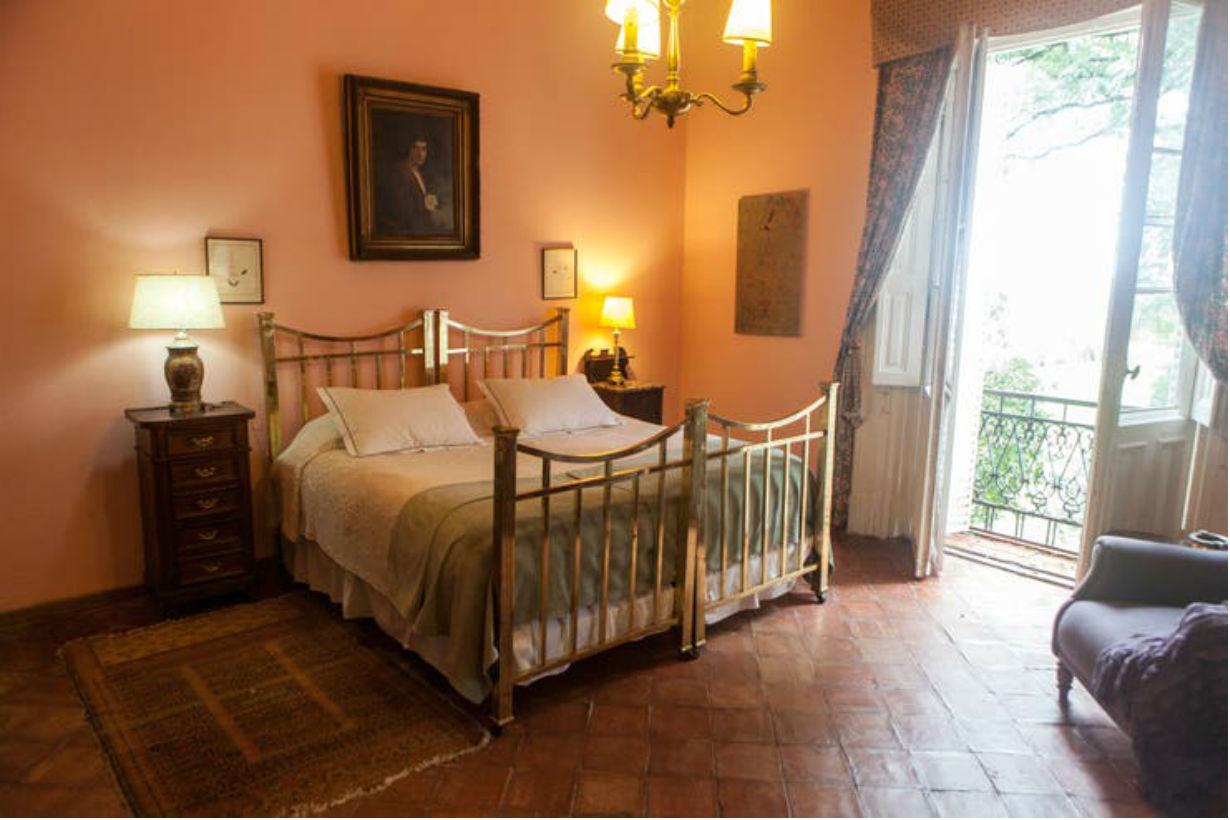 Camas de bronce y baldosones coloniales en una habitación en Santa Cándida.