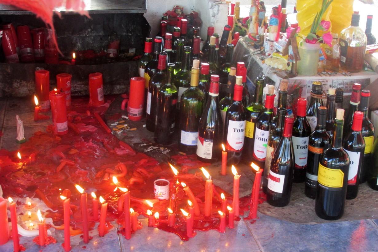Velas rojas, botellas de vino y cigarrillos encendidos en torno a la figura del santo pagano.