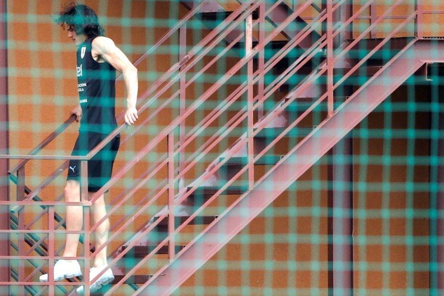 Con dificultad, Cavani baja las escaleras.