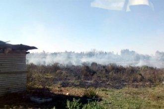 Mientras los bomberos trabajaban para sofocar el incendio, alguien prendía fuego un campo cercano